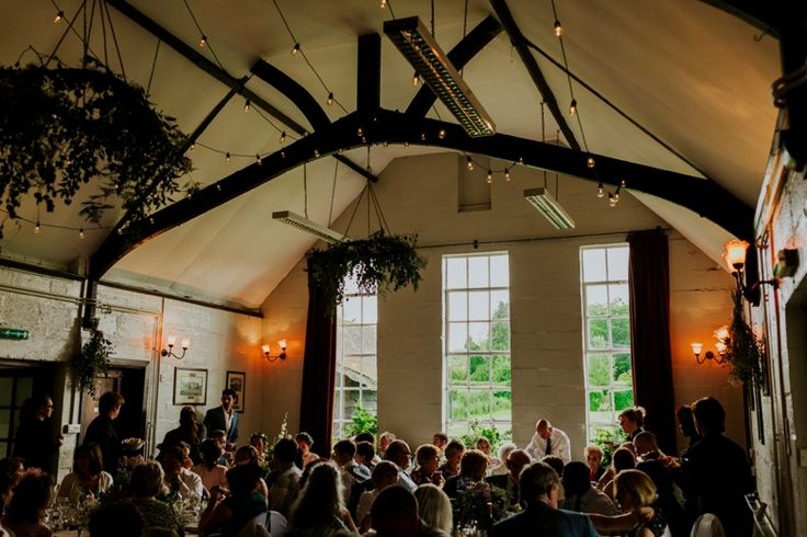The lovely flower-filled interior of Wytham Village Hall, Oxfordshire. Photo by Benjamin Stuart Photography #weddingphotography #weddingvenue #villagehall #wytham #countrywedding #weddingdecor #flowers #festoon
