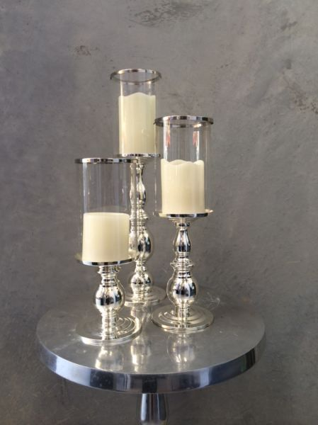 3 x Silver Hurricanes with pillar candles Presented on mirror base with tea lights