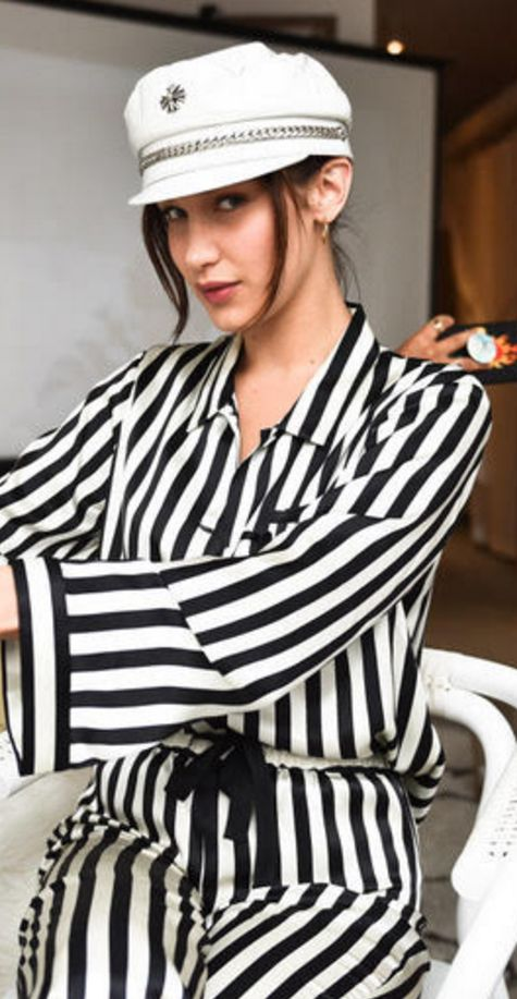 Who made  Bella Hadid's black stripe top and white striped pants?