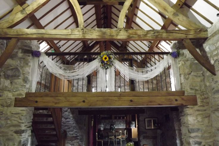 Gallery at Plas Isaf Corwen, with organza swagging, and flowers in the centre, hydrangea heads at ends  www.weddingflowersbylaura.com