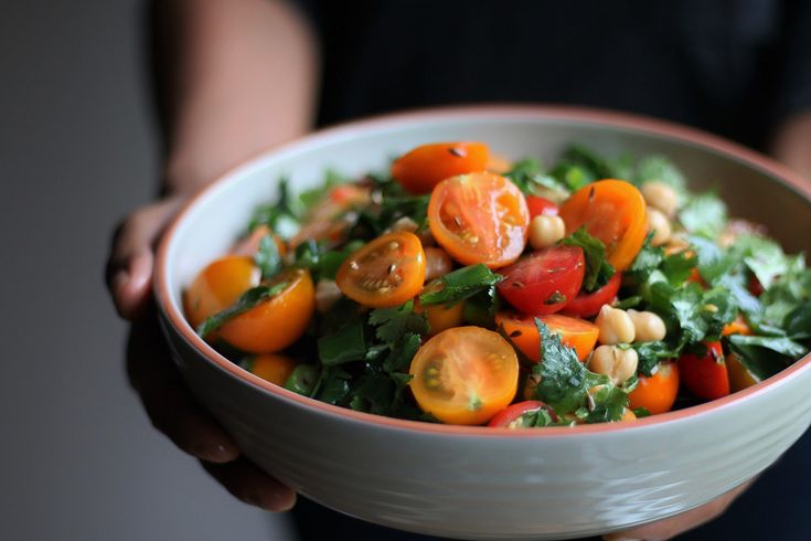 Sun gold cherry tomatoes and chickpeas colourful spring salad.