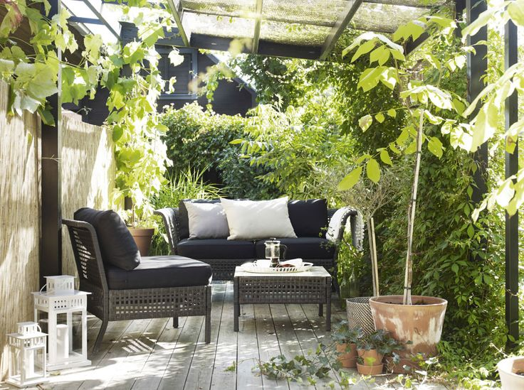 A small terrace furnished with a coffee table, a two-seat sofa and an easy chair, all in black-brown plastic. Completed with cushions in black, beige and gray.