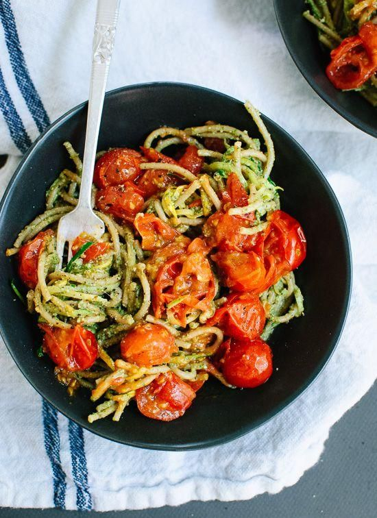 Homemade pesto tossed with squash noodles and spaghetti, topped with burst cherry tomatoes.
