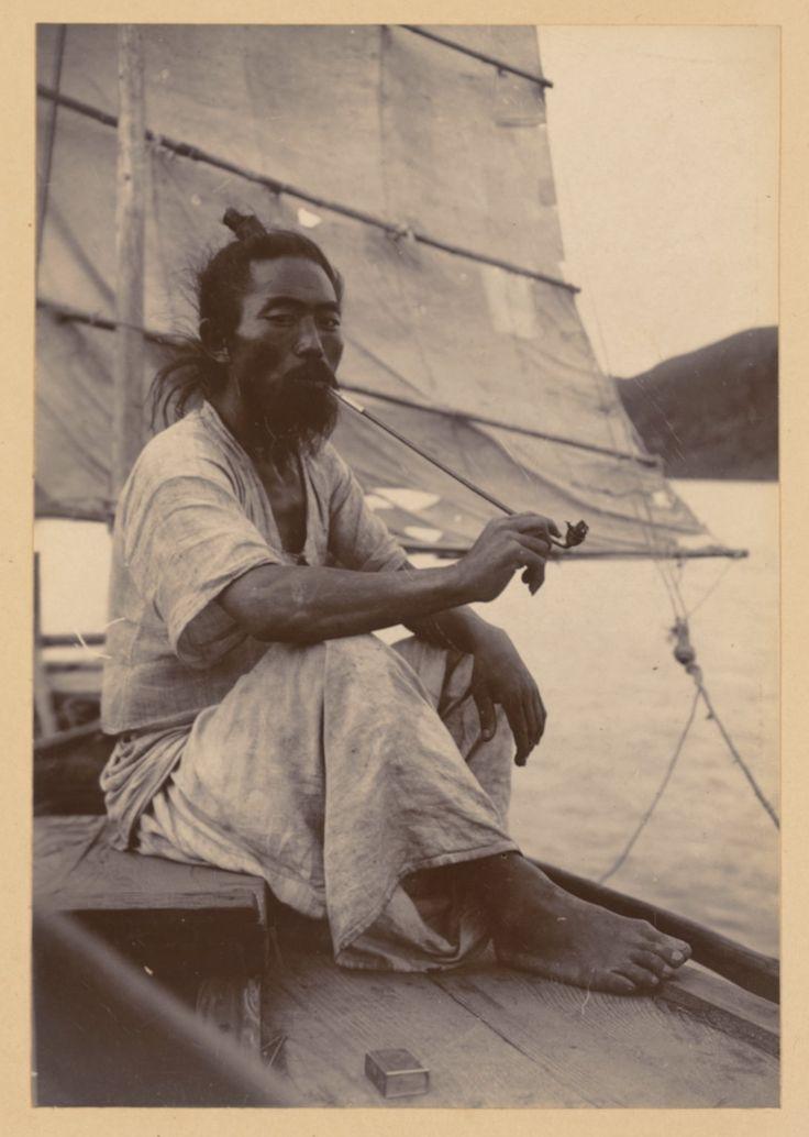 (1904 년경) 한국어 선원은 그의 긴 대나무 파이프에서 흡연, 항해에서 그늘 아래 앉아화물과 사람을 수송에서 휴식을 취합니다.  그는 멋진 대마 옷을…