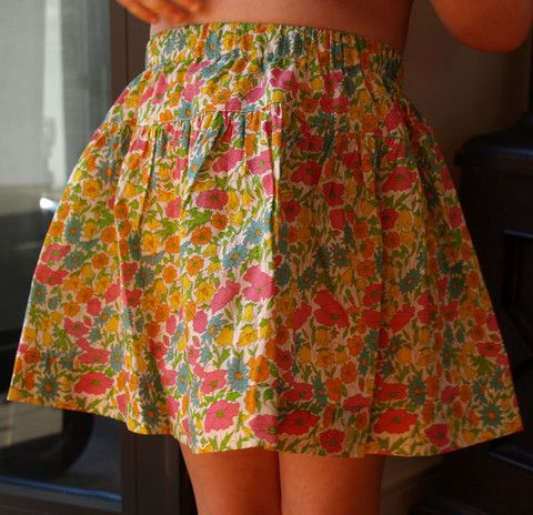 Tout Petit designed and made Liberty Tana Lawn Poppy and Daisy J skirt, with pink, yellow, blue and orange floral detail.  100% Tana Lawn cotton, made in Denmark. Elasticised waist, with ruffle style skirt.   In size 2 only $76.95