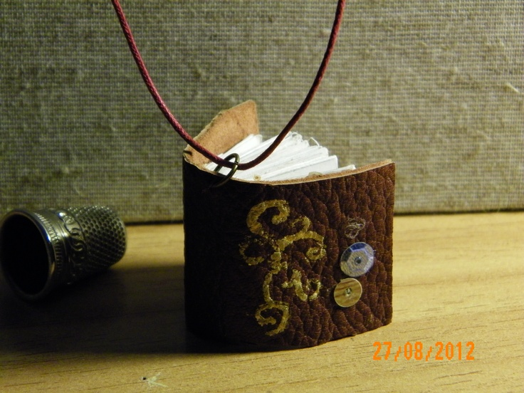 Leather hand-stitched mini book pendants. The color and design of the covers can easily be customized