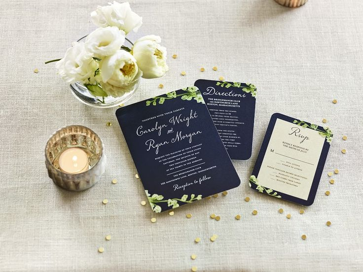 A photograph of a wedding invitation, directions card, and an RSVP card.