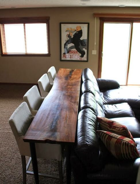 Table and barstools behind couch. Would be cool in a man cave.