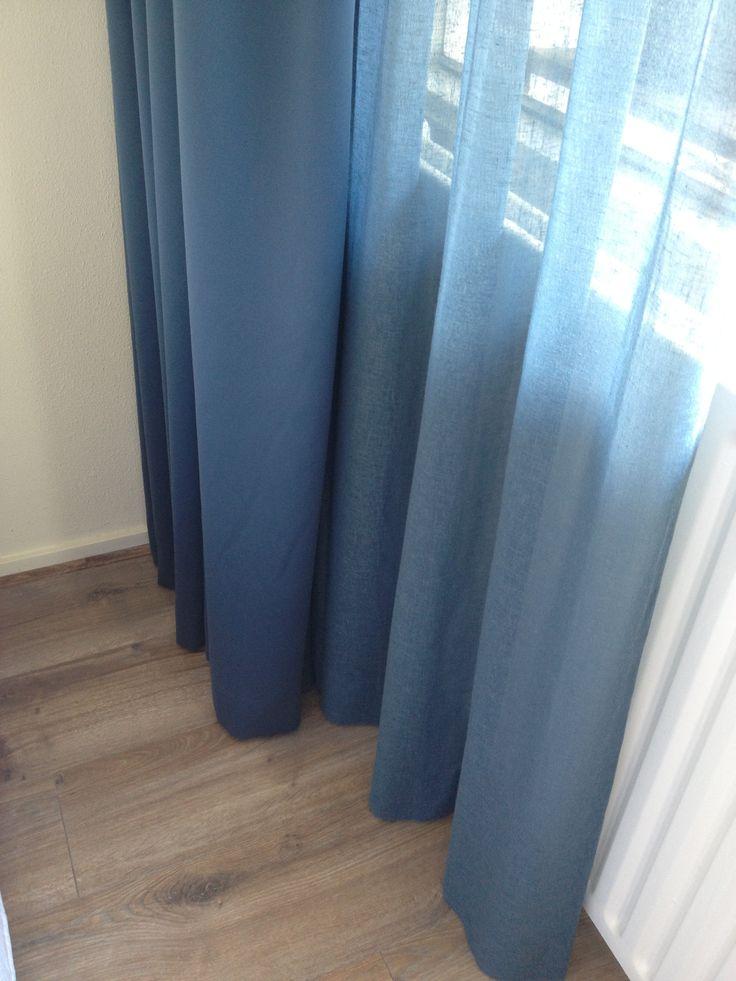 Gordijnen in de slaapkamer; verduisterende gordijnen en in-betweens in dezelfde kleur blauw.
