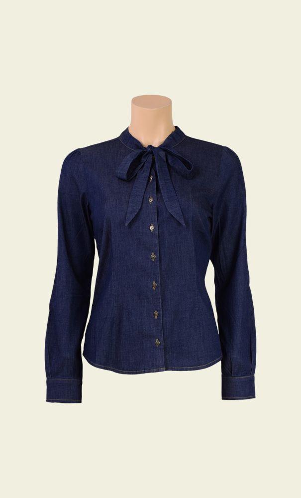 De klassieke denimblouse met een vrouwelijke twist! Deze blouse van lichte denim stof heeft namelijk een strik sluiting in de hals. Op de voorkant heeft de blouse kleine metalen knoopjes en de schouders zijn licht gepofd voor een speels effect.