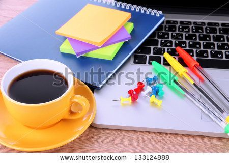 Laptop with stationery and cup of coffee on table - stock photo