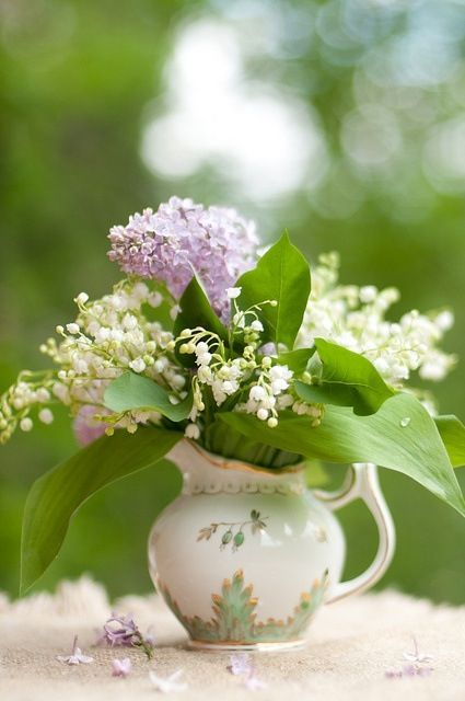 A little arrangement in a teapot — lily of the valley and lilac.