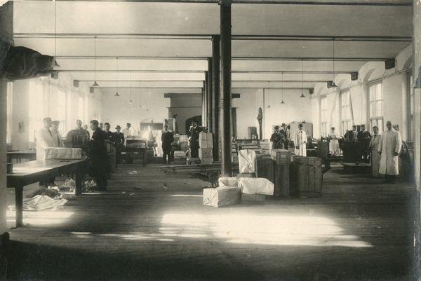 Århus Toldkammers vejerbod, ca. 1929. Toldere i hvide kitler er i gang med at pakke ud, veje og tarifere.