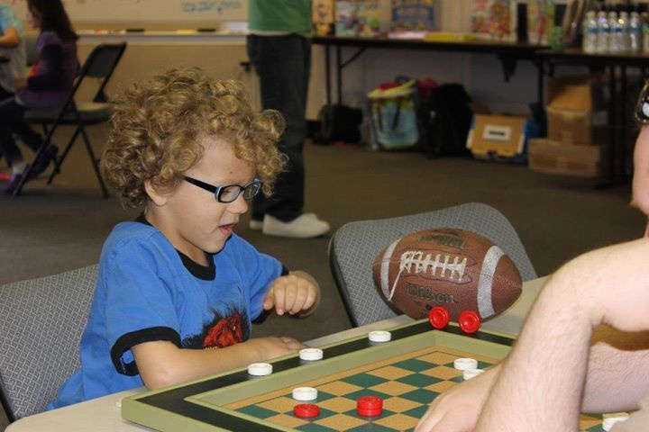 This little guy is enjoying a game of checkers on the Light Green Tournament Checkerboard