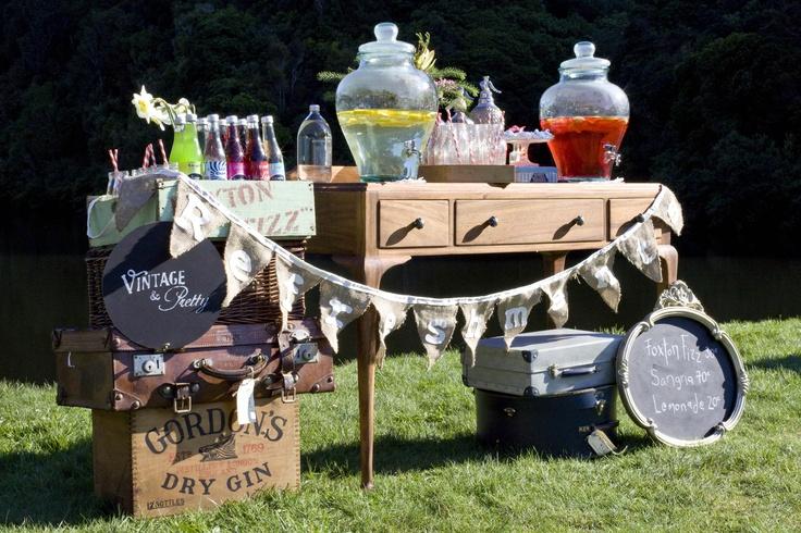This is a Vintage & Pretty colourful rustic & whimsical retrospective table.   Venue: Zealandia, Karori, Wellington  Featuring: Foxton Fizz, Shangri Las, wooden crates, suitcases, Decorada swirl meringues & more.