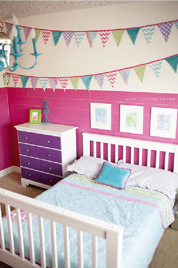 This DIY little girl's bedroom is a dream come true! A bright pink and purple color scheme keeps the room feeling fun and playful while homemade decorations give it a personal touch. Learn how you can make a kid-friendly gallery wall or a DIY banner to decorate your little one's big kid bedroom today.