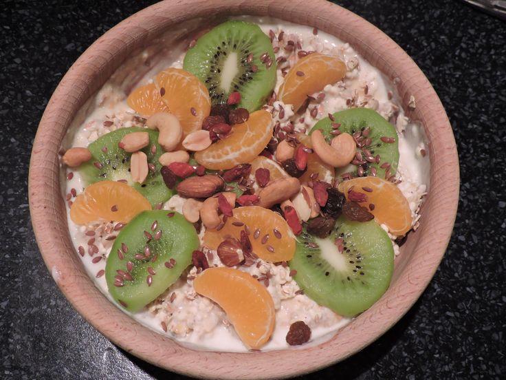 Ovesné vločky, tvaroh, kefír, pohankové pukance, půlka kiwi, mandarinka, goji, aršíďák, mix ořechů a rozinek, kokos, chia, lněné semínko, meruňky