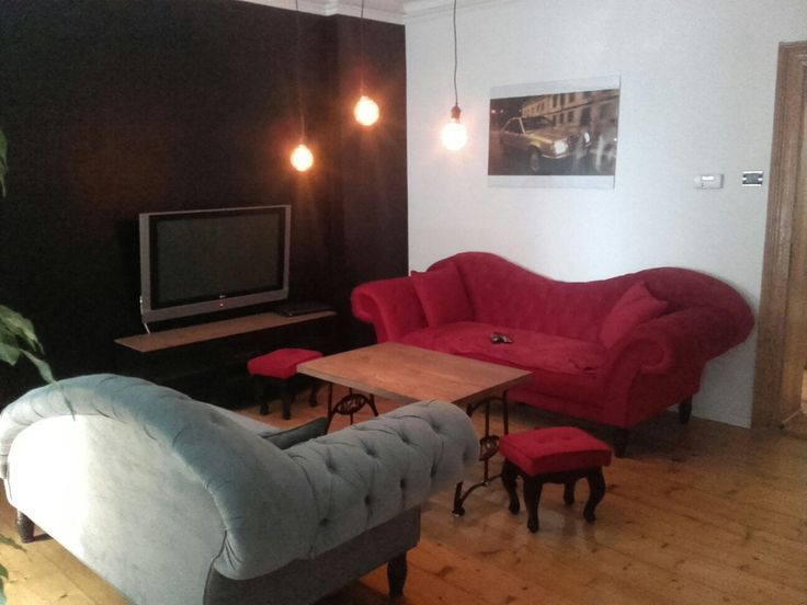 Red sofa* Black wall* Sewing machine table* wooden floor*  Edison bulb*