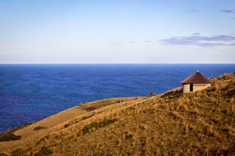 Transkei, Eastern Cape, South Africa. Close to East London South Africa. That's the warm Indian Ocean. The huts are called rondavels and typically have thatched roofs.