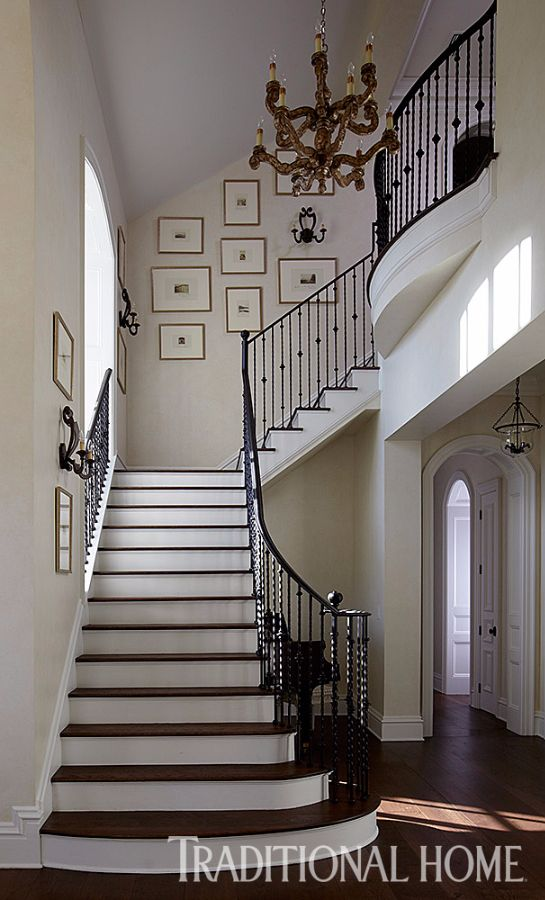 Barley-twist iron railings amp up the drama on this beautiful staircase. - Photo: Colleen Duffley / Design: Andrew Howard