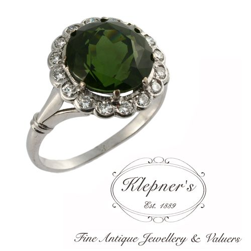 18ct white gold vintage green tourmaline & diamond flower cluster ring,  circa the 1960s, centrally claw set with one 6.17ct round green tourmaline, surrounded by a halo of rub set round brilliant cut diamonds. Visit us at www.klepners.com.au