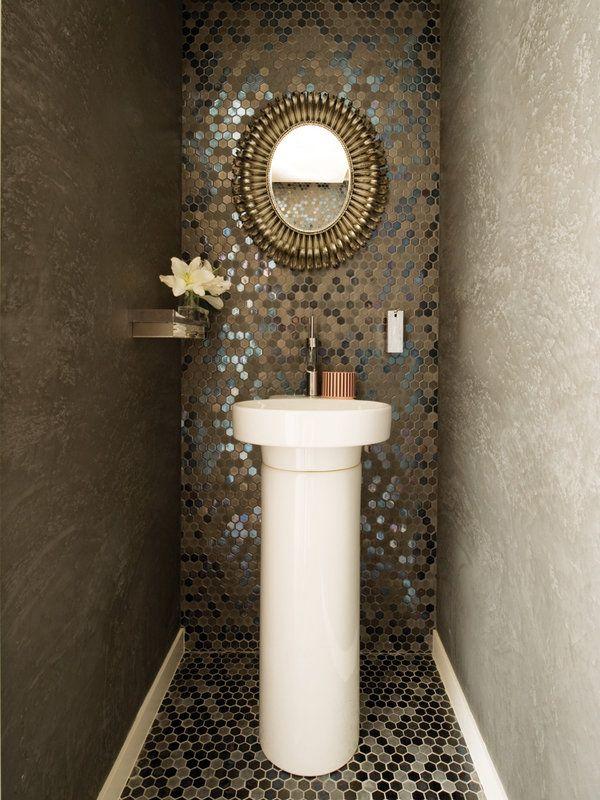 UN ASEO DE INVITADOS MUY COQUETO La pared central y el suelo cuentan con un revestimiento de mosaico hexagonal Light Gigacer con acabado metalizado, de Azulejos Peña. También de esta tienda son el lavabo de columna Orbis y la grifería.