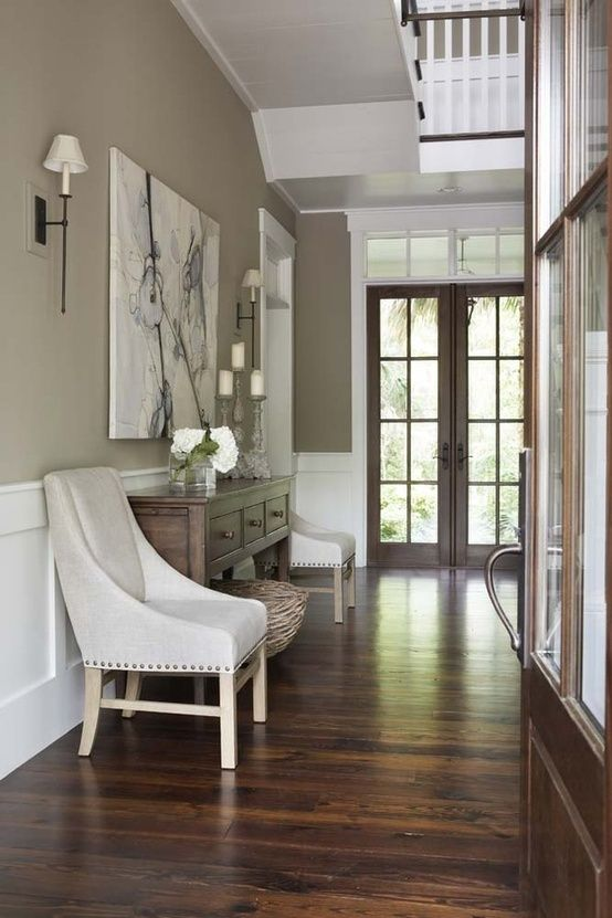 Tasteful hallway. The dark floor contrasts beautifully with the light, soft coloured walls.