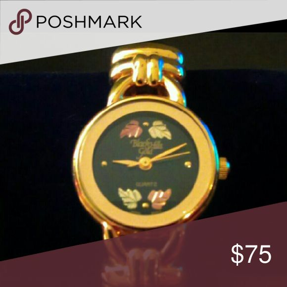 """Black Hills Gold Watch Black Hills Gold Ladies Watch. It says Black Hills Gold on the face.  Gold tone case, lug and end pieces on the cuff, face is black with 12K Gold Leaves. The retractable band has black patent """"croc"""" pattern. Works perfectly. Black Hills Gold Jewelry Bracelets"""