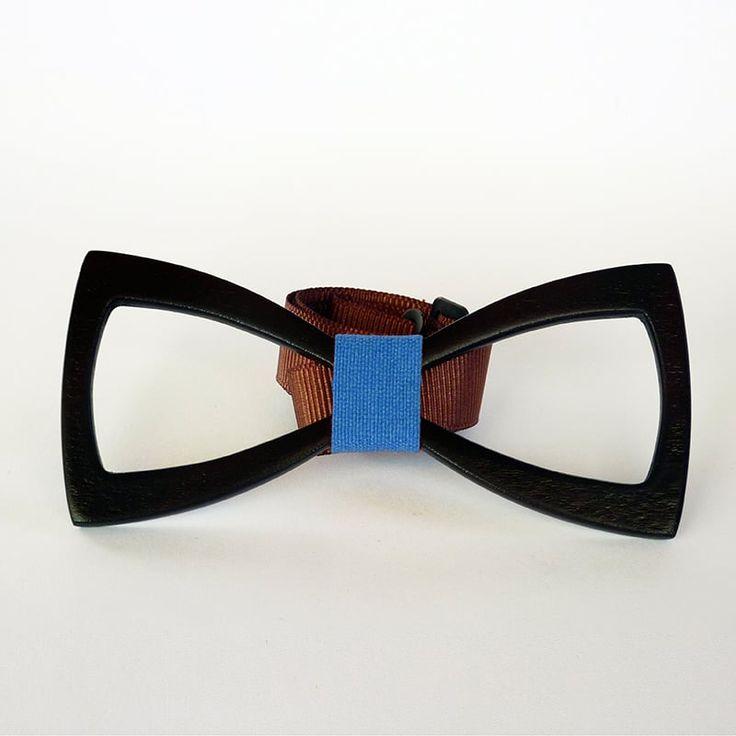Изящный галстук в подарок из натурального дерева (ольха) выполнен в виде вырезанного легкого контура бабочки. Изделие вскрыто экологически чистым лаком на водной основе оттенка черного каштана и украшено лентой – перевязью яркого голубого цвета.Бабочки – галстуки нынче снова на пике