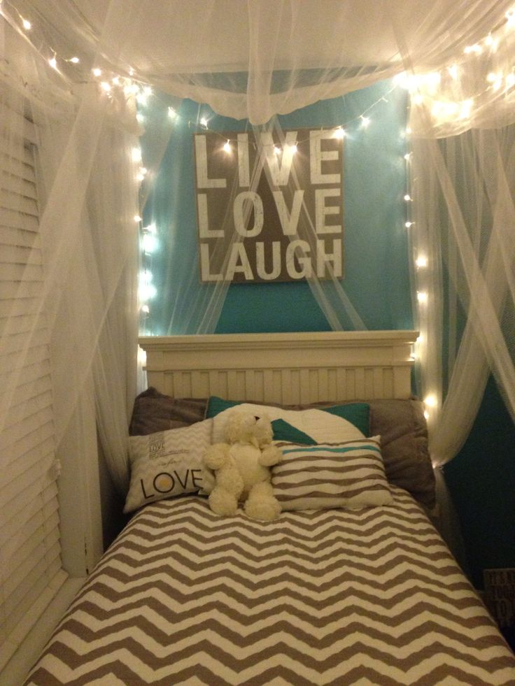 Bed canopy netting with fairy lights. We did this with my teen daughter's bed. I wish I had this as a teen. The live love laugh sign is highlighted above the headboard.