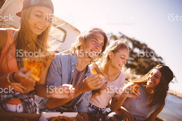 Teenaged friends sitting together outside eating pizza royalty-free stock photo