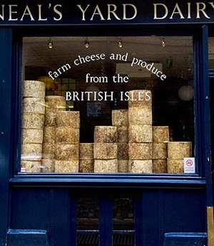 "Neal's Yard Dairy is a London artisanal cheese retailer and (formerly) cheesemaker, described as ""London's foremost cheese store."". The store is considered as a forerunner of the British wholefood movement and an important part of the revival of London's Covent Garden district. Founded in 1979 by Nick Saunders and Randolph Hodgson as a cheesemaker's shop, one of their first customers was Monty Python's John Cleese."