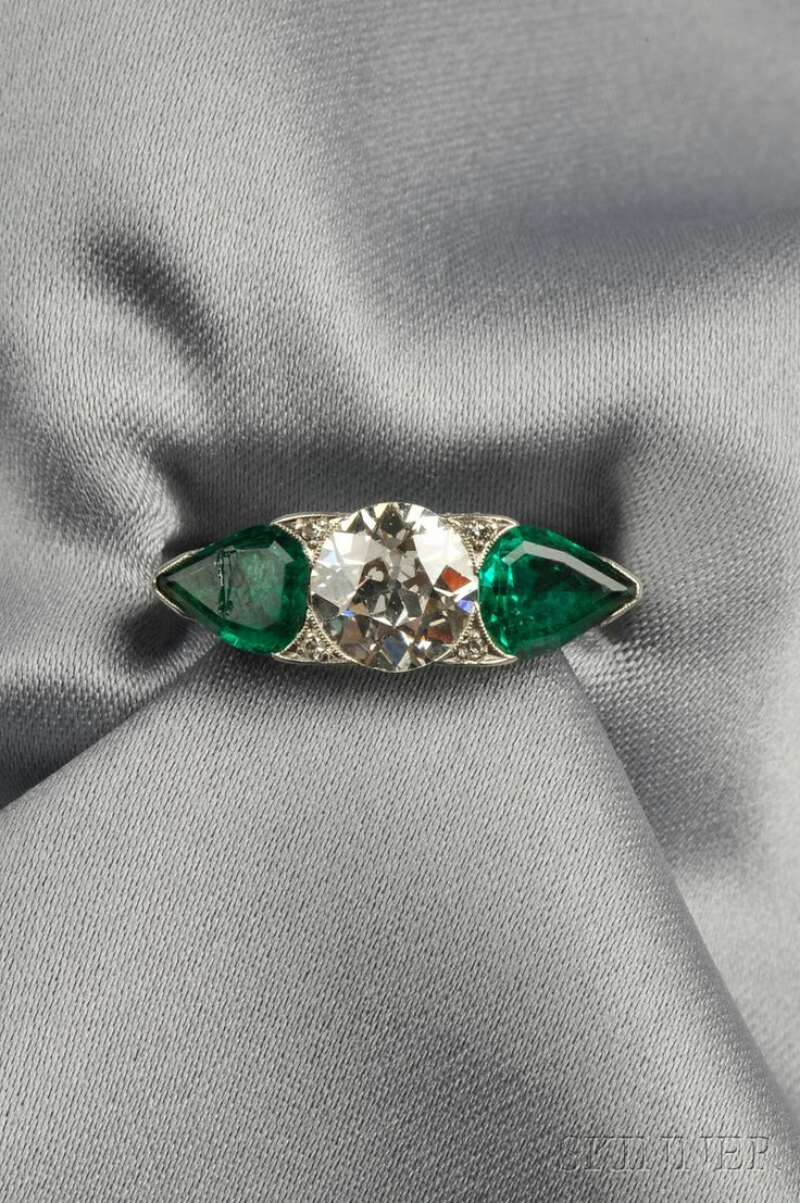 Art Deco Platinum, Emerald, and Diamond Ring, set with an old European-cut diamond weighing approx. 1.70 cts., flanked by pear-shaped emeralds, single-cut diamond melee accents, millegrain and engraved details