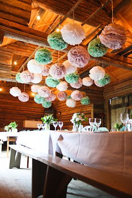 Mixed colours are going to be big in 2014, this is a gorgeous display of pom poms over a banqueting table - spot the festoon canopy over the beams