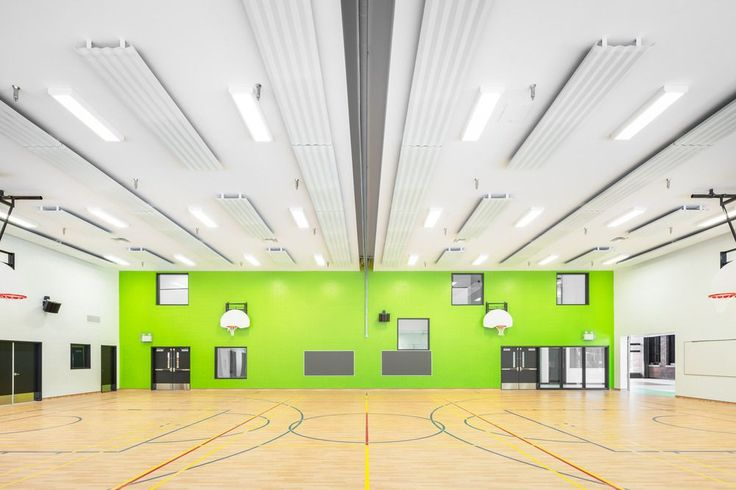 Tangy green color defines one of the gymnasium's walls & is echoed on  small storage boxes