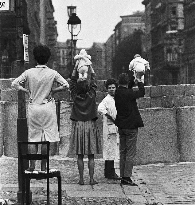 Berlin Duvarı'nın diğer tarafında kalan akrabalarına göstermek için bebeklerini yukarıya kaldıran çift, 1961.
