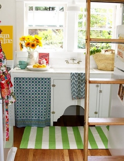 Tiny cottage kitchen - I love the use of a curtain below the sink and always have. One day I will do that. I love the white, too. Cheerful space.