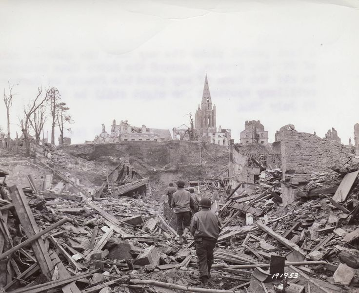 An American patrol enters the wrecked city of St. Lo, France. July 1944.