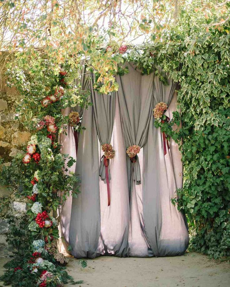 An Elegant California Wedding Inspired by the Comfort of Home | Martha Stewart Weddings - Inspired by elements within the property's ruins, the stone color of the drapery hinted at the rocks of the old winery's walls. And the hanging flowers (mostly proteas, lipstick pods, hydrangea, and eucalyptus) pulled in elements within the bridal party's bouquets, and created the illusion that the backdrop might be part of the landscape itself.