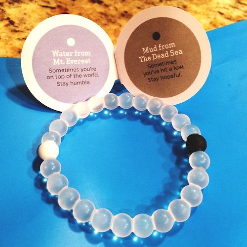 """""""The bracelet is infused with elements sourced from the highest and lowest points on Earth. The white ball, carrying water from Mt. Everest, and the black ball, holding mud from the Dead Sea, exist on opposite ends. A string of clear beads link the two, signifying that throughout life's circular journey, your path is your own."""""""