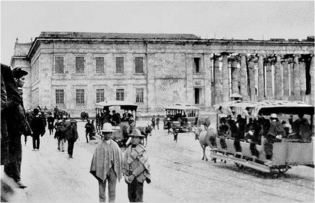 La Bogotá City Railway, conocida también como Ferrocarril de Bogotá (Colombia), inauguró el servicio de tranvías el 1º de dic. de 1884: desde el Parque de Santander subiendo por la Carrera 7 hasta la Calle 26, luego a través de la Carrera 13 hasta la Calle 67 en el barrio de Chapinero. El depósito de tranvías estaba en la Calle 57. La BCR extendió la línea poco después hasta la Plaza de Bolívar, mostrada en esta fotografía sin fecha. [Claudio Bellon]: Courtesy: Allen Morrison, New York…