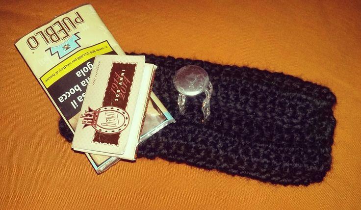Porta tabacco in lana nera con applicazione di bottone argentato.