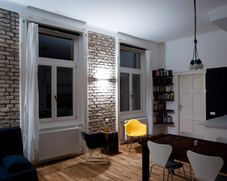 Raw brick wall, an orignal in the century-old building. Eames replica chairs, tailer-made floating bookshelves, and an ammo-case repurposed as a mini-table