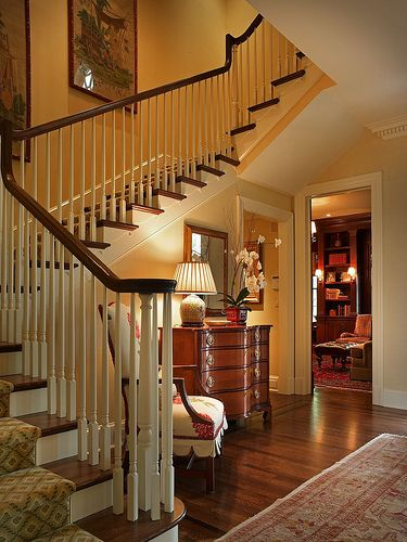Stunning foyer....wood floor, chest, rug, curving staircase, view into another room (Catlin Design)