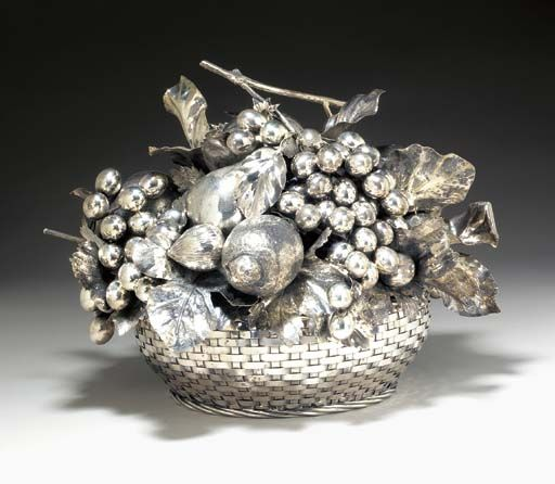 A SILVER FRUIT BASKET TABLE ORNAMENT, BY MARIO BUCCELLATI  The woven sterling silver basket, topped by a removable textured and sculpted sterling silver arrangement of fruits and leaves, the grape stem acts as the handle, 15 x 15 x 11 ins., 2028 dwt, 3155 g Signed M. Buccellati for Mario Buccellati