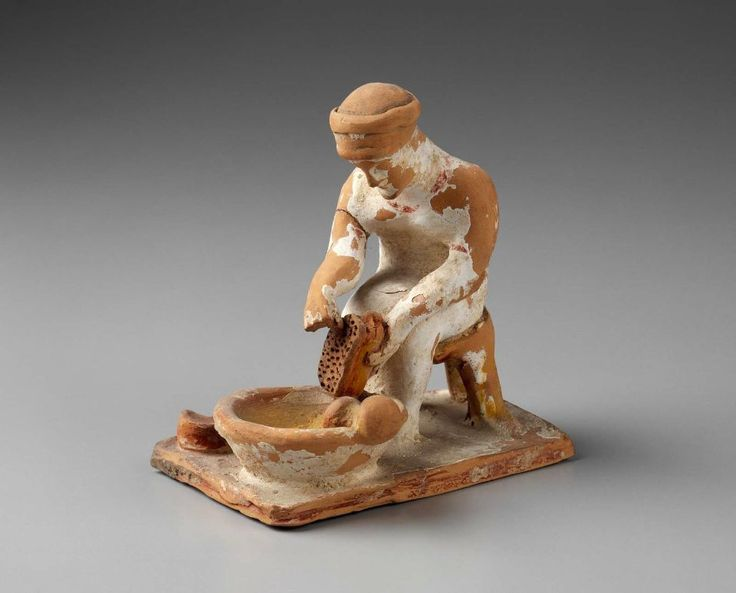 Woman grating cheese  Greek, Late Archaic Period, Early 5th century B.C.  PLACE OF MANUFACTURE  Tanagra, Boiotia, Greece  Statuette of woman grating cheese. On the edge of the bowl is a pestle; on the ground a cheese with a knife resting on it. The chiton is white with red around neck and sleeves. The edge of the base is red, the top white. The cheese red. Grater, (add Greek) chair, knife-handle, pestle, and inside of bowl are yellow. Lips red. Flesh white.