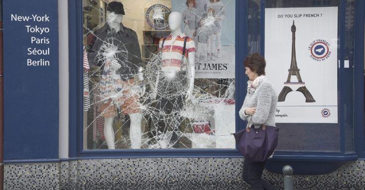 """20160514 - Francesa passa diante de vitrine quebrada em Rennes, no oeste da França, após confronto entre policiais e manifestantes durante a madrugada, parte do movimento """"Nuit debout"""". O movimento, liderado por jovens, começou em 31 de março para protestar contra a proposta do governo francês de reforma trabalhista, e vem se ampliando desde então Imagem: Damien Meyer/AFP"""