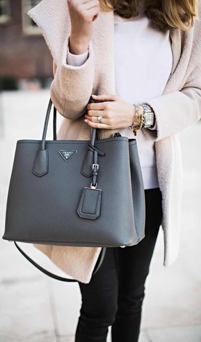 Emily Jackson is wearing a grey suede double bag from Prada. You can carry it around.