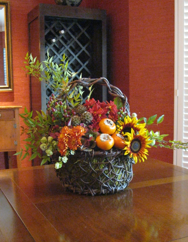 Grapevine basket filled with seasonal flowers, vines, berries, herbs and fruit for Thanksgiving table or sideboard.
