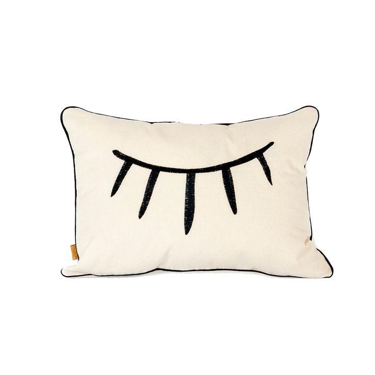 Cojín Ojo Cerrado ilustrado a mano y bordado en tela cruda con bordados negro. Este producto es ideal como complemento de decoración en camas, sillas o sofas.